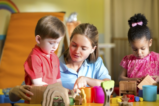 Nursery-teacher-supervising-children-playing-with-building-blocks